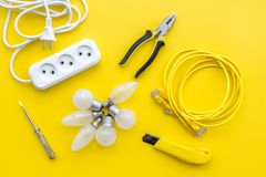 Electrical repair. Bulbs, socket outlet, cabel, screwdriver, pilers on yellow background top view. Electrical repair. Bulbs, socket outlet, cabel on yellow royalty free stock photography