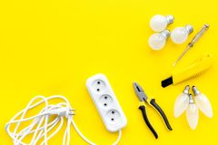Electrical accessories at home. Bulbs, socket outlet, cabel on yellow background top view copy space. Electrical repair. Bulbs, socket outlet, cabel on yellow stock images