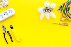 Electrical accessories at home. Bulbs, socket outlet, cabel on yellow background top view copy space. Electrical repair. Bulbs, socket outlet, cabel on yellow royalty free stock photo