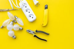 Electrical accessories at home. Bulbs, socket outlet, cabel on yellow background top view copy space. Electrical repair. Bulbs, socket outlet, cabel on yellow stock photos