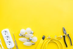 Electrical accessories at home. Bulbs, socket outlet, cabel on yellow background top view copy space. Electrical repair. Bulbs, socket outlet, cabel on yellow royalty free stock images