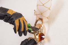 Electrical repairs sconce. Electrician with pliers in his hand repairing a sconce Royalty Free Stock Photography