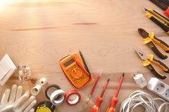 Electrical repairs tools on wood table with flare stock photography