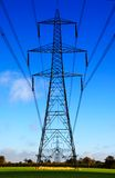 Electrical sentries. Electricity pylons in the English countryside Stock Photos