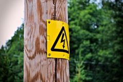 Electrical sign on a wooden post with blurry background. royalty free stock images