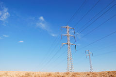 Electrical sky. Electrical pylons on background of blue sky and clouds Royalty Free Stock Images