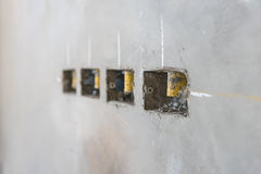 Electrical socket hole on precat concret wall, outlet electric w. Ires in constuction site stock photos
