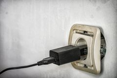 Electrical socket outlet falling out of wall. Old European electrical socket outlet falling out of wall and in need of repair royalty free stock photography