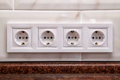 Electrical sockets on a kitchen tile wall royalty free stock photography