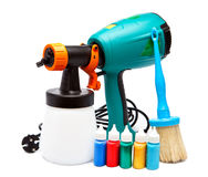 Electrical spray gun for coloration and a paintbrush and small bottles with color Royalty Free Stock Photos