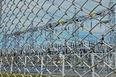Electrical substation behind wire chain fence Stock Images