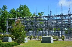 Electrical Substation. Large electrical substation fenced in on a piece of well landscaped land with shrubs and small trees and large Pine Trees in the Stock Images
