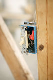 Electrical Switch Closeup. Closeup of an electrical switch box nailed to a wood beam on a construction site. Shallow depth of field with focus on switch. Room royalty free stock photography