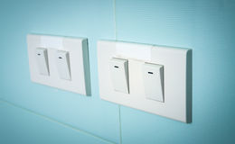 Electrical switch. Electrical white rocker light switch on green wall Stock Image