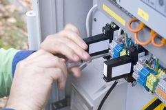 Electrical system. Hands of an electrician at an electrical switchgear cabinet royalty free stock photo