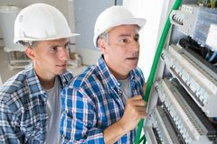 Electrical team installing fuse box. Electrical team installing a fuse box royalty free stock photos