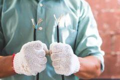 The electrical technician is holding the power cord for installation.  stock photos
