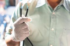 The electrical technician is holding the power cord for installation.  stock image