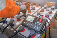Electrical technician use milli ohm meter to measure internal resistance and voltage of batteries Royalty Free Stock Photography