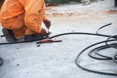 Electrical with tool cuts electrical cable Stock Image