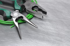 Electrical tools and cables on metal surface with place for text. Green electrical tools and cables on metal surface with place for text Stock Photography
