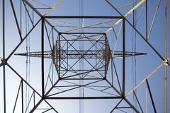 Electrical Tower Inside. High-tension electrical tower looking up from the inside against a clear blue sky Royalty Free Stock Image