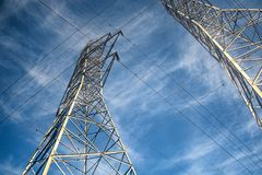 Double Exposure of Pylons. Electrical tower pylon with wires on a blue sky with clouds Stock Photos