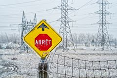 Electrical power field with freezing rain. Electrical tower and stop sign near a power plan field with freezing rain in Laval, Quebec, Canada royalty free stock photos