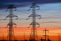 Electrical Towers with Colored Sky. Electrical towers are silhouetted against a colorful sunset sky Stock Photos