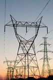 Electrical Towers (Electricity Pylons) at sunset. A long line of electrical transmission towers carrying high voltage lines at sunset Stock Photos