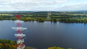 Electrical towers located near peaceful river against landscape. Aerial view electrical towers located near peaceful river with sky reflection against green stock footage