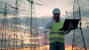 Electrical transmission line and a male worker speaking on a phone. HD stock footage