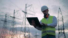 Electrical transmission lines and a male inspector working beside them. HD stock footage