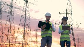 Electrical transmission lines and two engineers with computers work using VR headset. Electrical transmission lines and two engineers with computers. HD stock footage