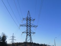 Power poles in the blue sky. Electrical transmission pylon. High voltage. Power poles in the blue sky stock photography