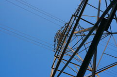 Electrical Transmission Tower from Below. An electricity transmission tower rises overhead, casting its metal frame against the blue sky, as power lines extend royalty free stock images