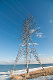 Electrical Transmission Tower (Electricity Pylon). An electrical transmission tower carrying high voltage lines beside a lake in winter Royalty Free Stock Photo