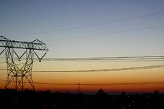 Electrical transmission tower at sunset. The geometry of a power line electrical transmission tower dominates the quiet landscape and colorful sunset. Energy stock images