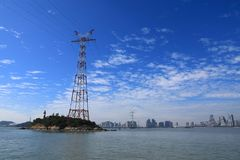 Electrical transmission tower under blue sky. Electrical transmission tower landscape onthe sea at xiamen city.Energy concept stock image