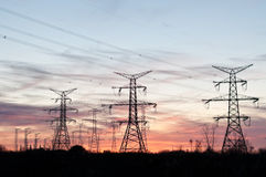 Electrical Transmission Towers (Pylons) at Dusk. A long line of electrical transmission towers carrying high voltage lines Royalty Free Stock Images