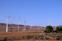 Electrical windmill being built near a farm house Stock Photos