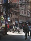 Electrical Wire Cable Tangled and Chaos at Thamel Street, Motorbike Rider Crossing, People Walking Wear Mask. Editorial royalty free stock photo