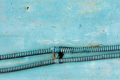 Electrical wire in metal reinforced hose against painted wall royalty free stock photo