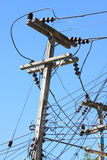 Electrical wire on pole. chaotic wire with nest on pole and blue sky background. Royalty Free Stock Images