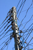 Electrical wire on pole. chaotic wire with nest on pole and blue sky background. Stock Images