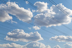 Electrical wires against blue sky and beautiful clouds Royalty Free Stock Photo