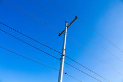 Electrical wires on a pole on blue sky background. Royalty Free Stock Images