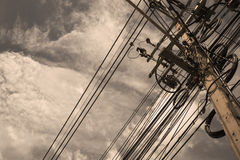 Electrical wires on a pole on a cloudy sky. Electrical wires on a pole on a cloudy sky Stock Photos