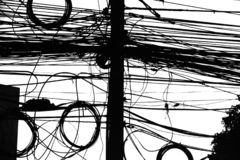 Electrical wiring in Thailand. Mess of cables in black and white stock photo
