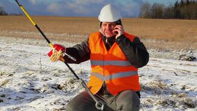 Electrical worker with cell phone near tensioner stock footage
